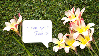 Note in shape of a chat bubble, with words Love you Dad! and flowers on green grass.