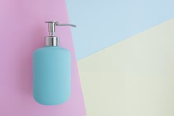 Minimal flat lay concept of blue shower gel, shampoo or cosmetic bottle on the colorful background with copy space