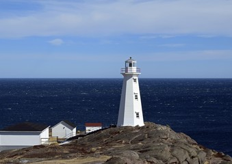 view towards the ocean at with the historic 19th century lighthouse in the foreground at Cape Spear National Historic site, Avalon region Newfoundland Canada