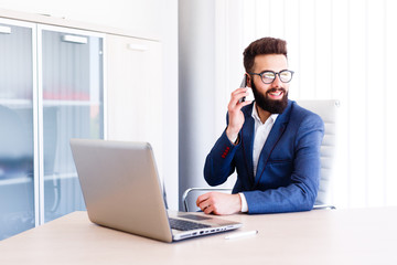 Young Banker Talking On Phone While Works On Laptop