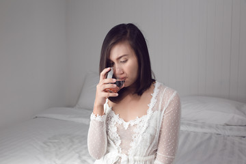 84d9b442d8 Asian woman in white nightwear drinking water before bedtime for ...