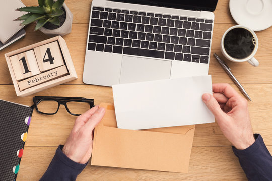 Man open envelope at workplace while working