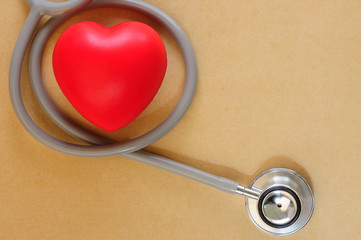 Healthcare medical insurance business and world heart health day concept with red heart with stethoscope on brown background