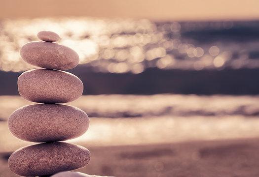 Vintage hipster style Zen meditation background, balanced stones stack on sea beach