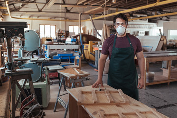 Young woodworker in protective workwear standing in his studio
