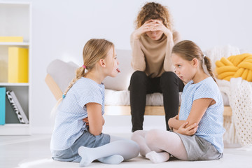 Sisters arguing and stressed mom