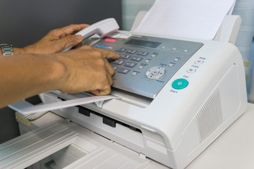 Men are using a fax machine in the office. Business concept