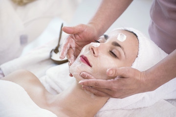 Masseur doing cream mask on face of beautiful young woman relaxing in the spa salon.