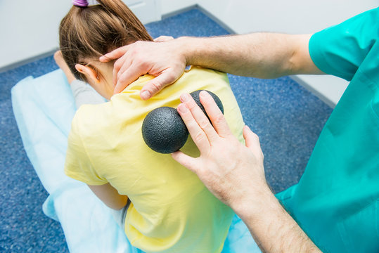 Woman at the physiotherapy receiving ball massage from therapist. A chiropractor treats patient's thoracic spine in medical office. Neurology, Osteopathy, chiropractic. Selective focus, Close up.