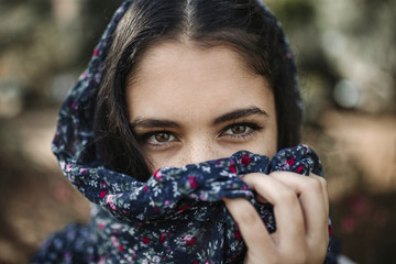 Close-up portrait of teenage girl with obscured face standing outdoors