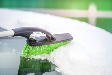 Removing snow from car with a brush