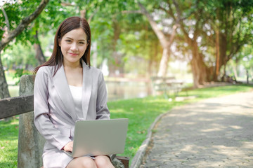 Portrait of Asian business woman using tablet on lunch break in city park.