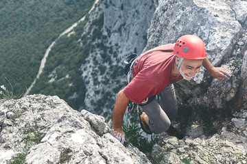 old-aged man rock climber climbs on the cliff