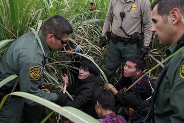 Border patrol agents apprehend immigrants who illegally crossed the border from Mexico into the U.S. near McAllen