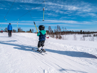 Young kid riding in a ski lift on his own. Small skies in a drag lift.