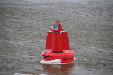 Red buoy with ice on river Hollandse IJssel during winter in the Nehterlands