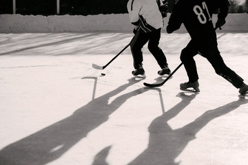 men play hockey on the rink during the day