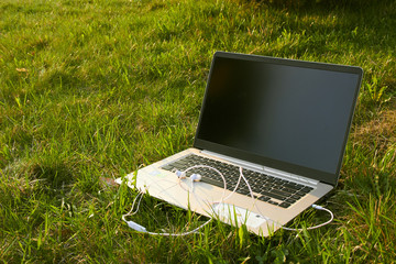 laptop with headphones stands on green grass