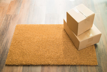 Blank Welcome Mat On Wood Floor With Shipment of Boxes