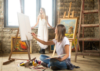 The woman model poses to a young woman painter
