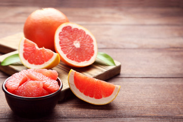 Ripe grapefruits slices in bowl on brown wooden table