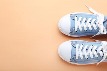 Pair of blue sneakers on orange background