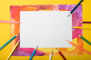 A frame with a kid drowing and colored pencils.
