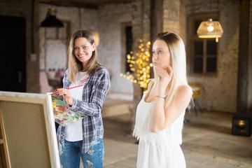 Young girl paints a portrait