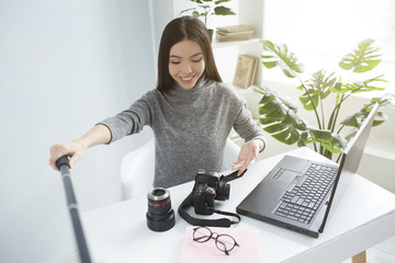 Dark-haired girl is sitting at the table and streaming a video. She is showing her equipment for photoshoots to her followers. She is excited and happy.