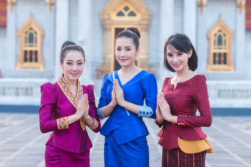 Beautiful Thai girl in Thai costume,Asian woman wearing traditional Thai culture standing in front at temple.