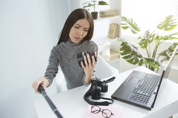 Professional blogger is sitting at the table and recording a video where she is looking to the camera's lens and studying it. She looks serious and cocncentrated.