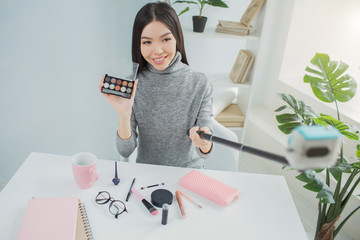 Girl is taking a selfie with the palette of shadows. She likes this beauty product. Girl is smiling and looking to the camera.
