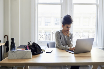 Businesswoman using laptop at desk in office