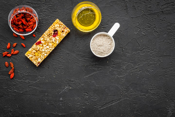 Granola bars with Goji berry on black background top view space for text