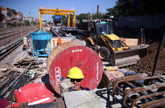 An employee works next to railroad tracks in Buenos Aires