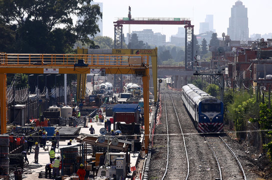 Employees work next to railroad tracks as a train passes by in Buenos Aires