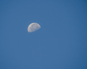 the half moon on the blue day sky