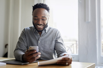 Smiling businessman using mobile phone while working in office