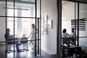 Entrepreneurs discussing in board rooms at creative office seen through windows