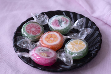Colorful lollipops and different colored fruit round candy in wrapper in plate