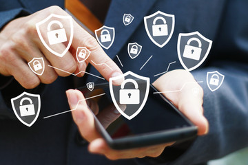 Businessman pressing button locked shield security virus on phone virtual electronic user interface.