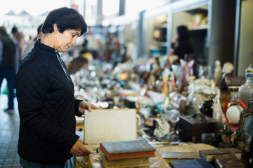 Thoughtful middle aged lady looking retro handicrafts
