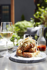 Chicken served on a wooden plate with a glass of white wine