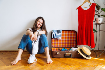 smiling woman sit on floor near valise with clothes. packing before trip. travel concept. copy space