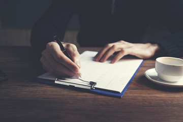 man hand document and cup of coffee on table