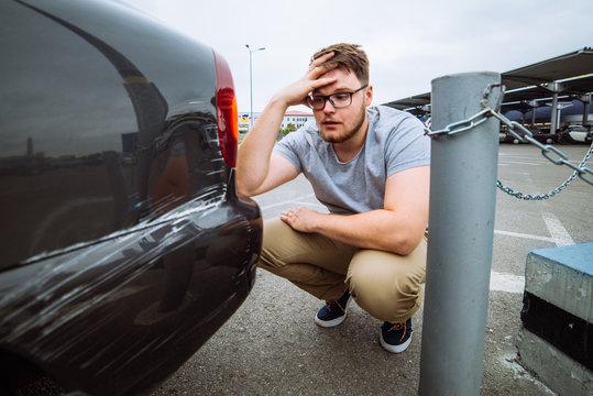 sad man sit near dint car with sad face. insurance case.