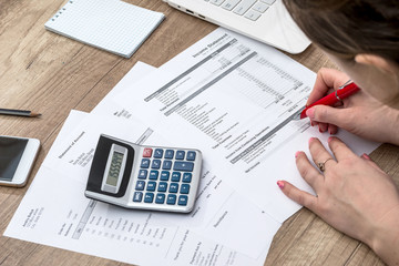 Woman counting her budget, hands with calculator