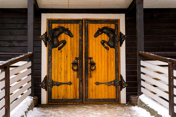 Original design, wooden doors with metal horses. Entrance to the stable in winter