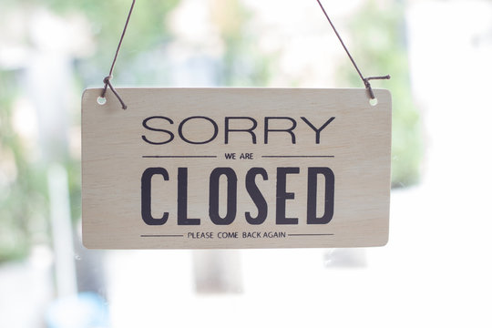 A sign hanging off Coffee shop door,Close sign blur background,Label word close