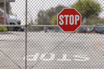 stop sign attached to chain link fence